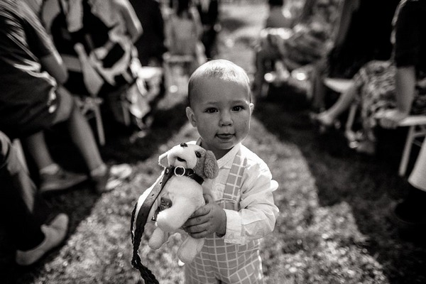 Young child carrying toy dog down aisle