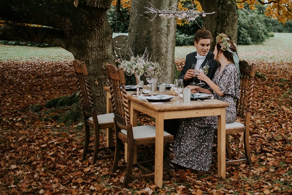 Bride and groom sitting at wedding table under tree