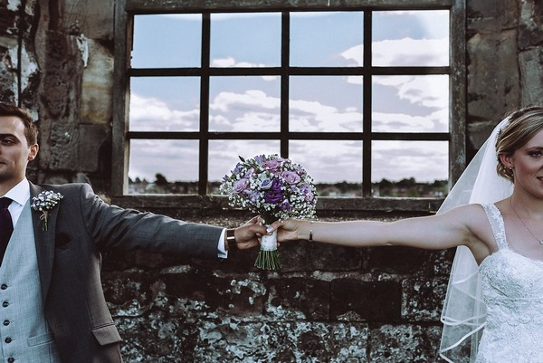 Bride and groom with arms outstretched holding bouquet