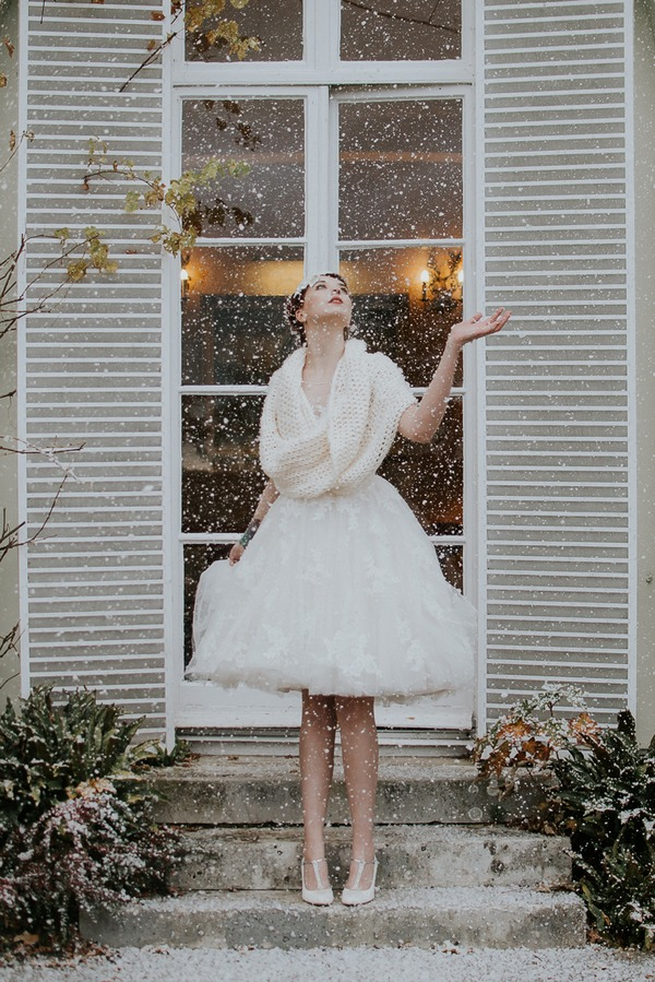 Bride holding out hand as snow falls