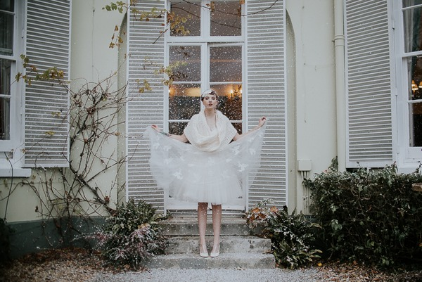 Bride holding out skirt of dress in snow
