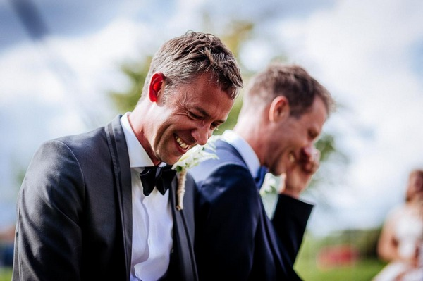 Grooms laughing and wiping away tears