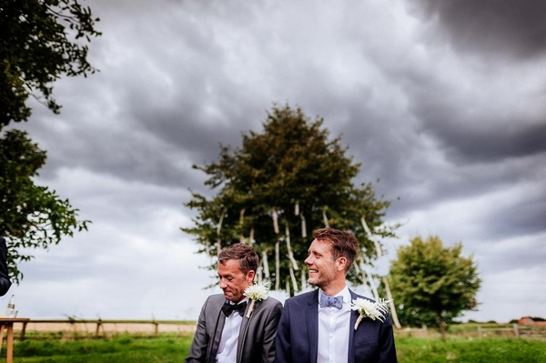 Storm clouds gathering over grooms at wedding
