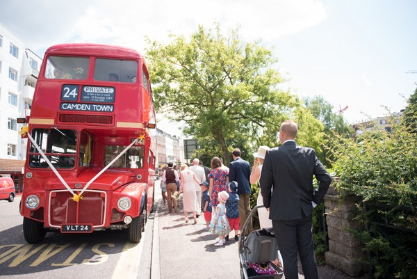 Wedding guests boarding red bus