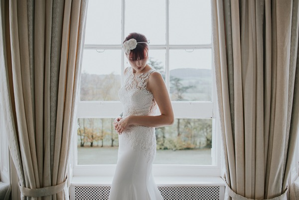 Bride looking down in front of window