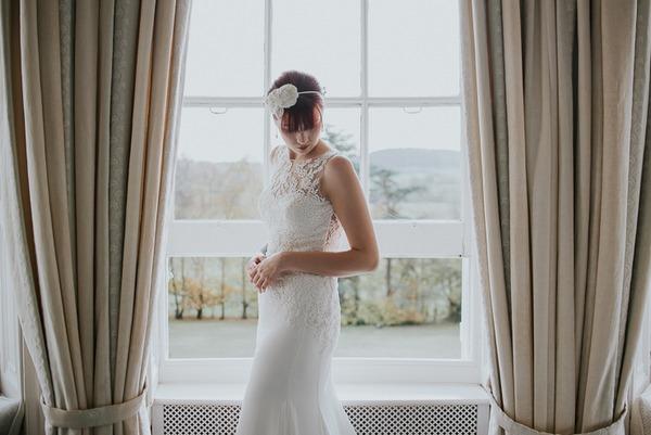 Bride looking down in front of window