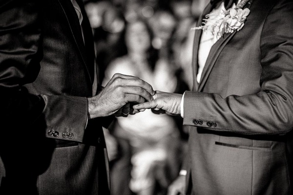 Grooms exchanging wedding rings