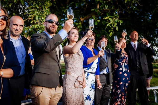 Wedding guests raising glasses for toast