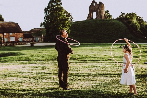 Man and girl playing with hula hoops