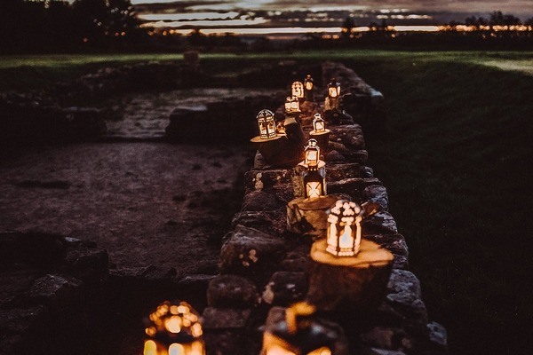 Lit lanterns in a row on wall