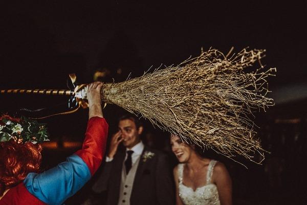 Medieval celebrant holding up broomstick