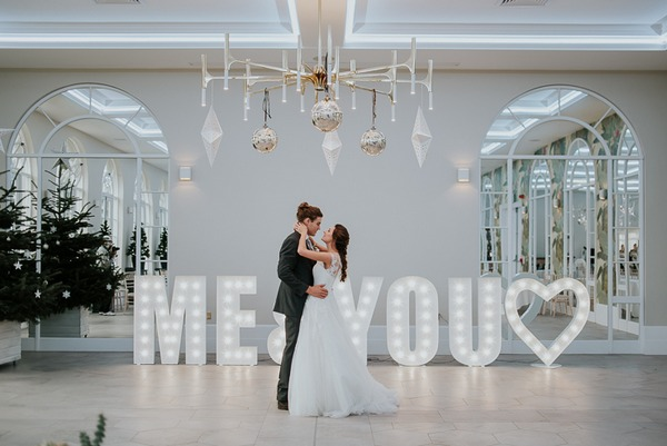 Bride and groom in front of large letters