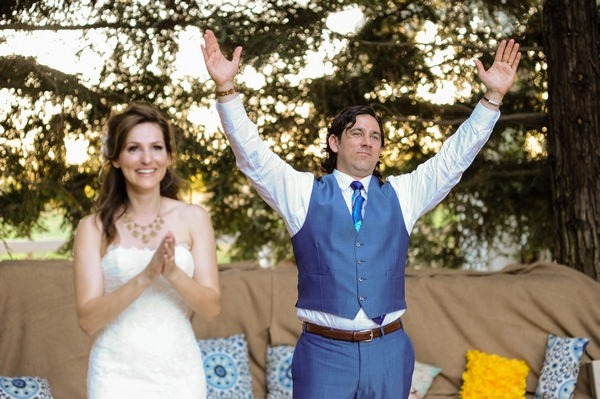 Groom holding arms up for applause after speech