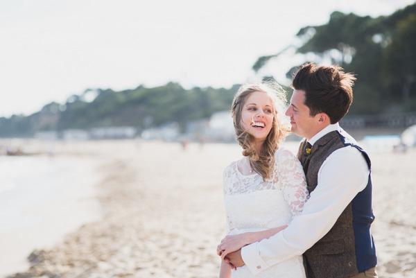 Groom with arms around bride's waist on beach