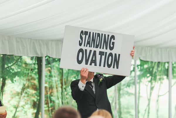 Holding standing ovation sign at end of wedding speech