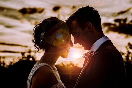 Bride and groom touching heads with sun shining between them