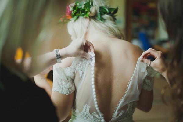 Doing up back of bride's dress
