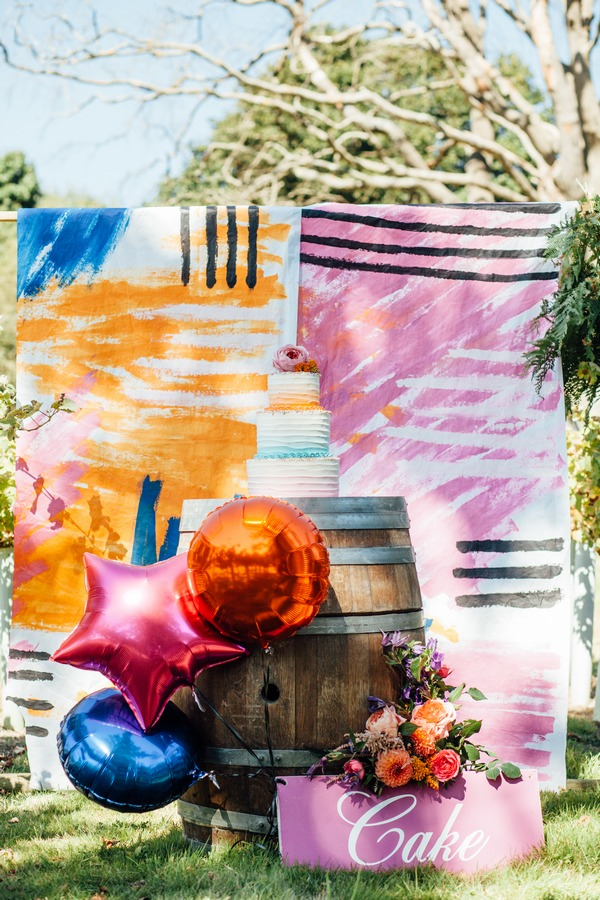 Wedding cake on barrel against colourful wedding backdrop