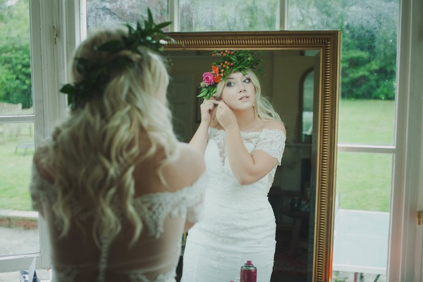 Reflection of bride in mirror putting on earrings