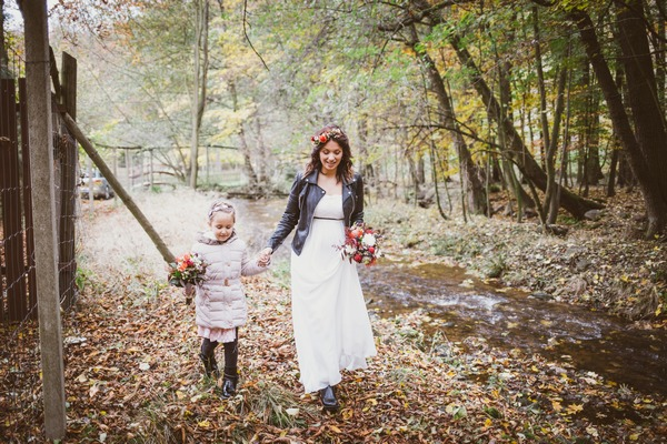 Bride walking through forest with flower girl