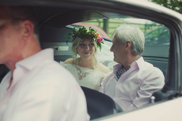Bride and father sitting in wedding car