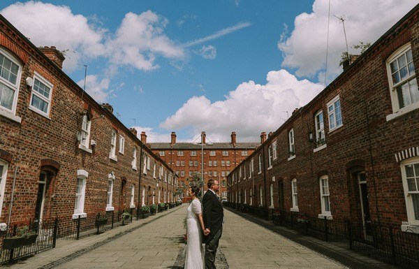 Bride and groom standing back to back in middle of street - Picture by Embee Photography