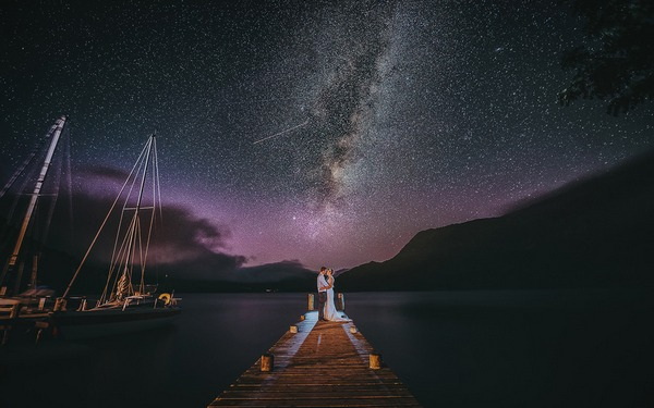 Bride and groom standing on jetty at night with incredible starry coloured sky - Picture by Richards and Co Photography