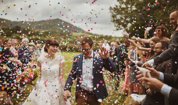 Bride and groom smiling as they walk through a shower of colourful confetti - Picture by Neil Jackson Photographic