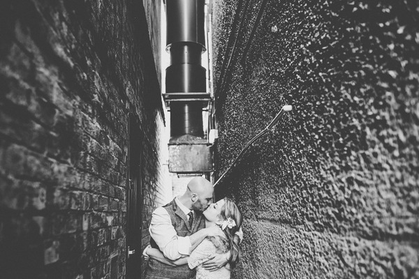 Bride and groom kissing down narrow alleyway - Picture by Helen Howard Photography