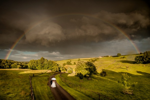 Bride and groom walking down road in beautiful countryside with darks clouds and rainbow overhead - Picture by Ian Baker Photography