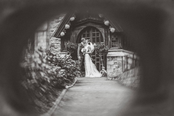 Picture taken through gate of bride and groom kissing outside church - Picture by Joy Foulds at Beautiful Life Photography