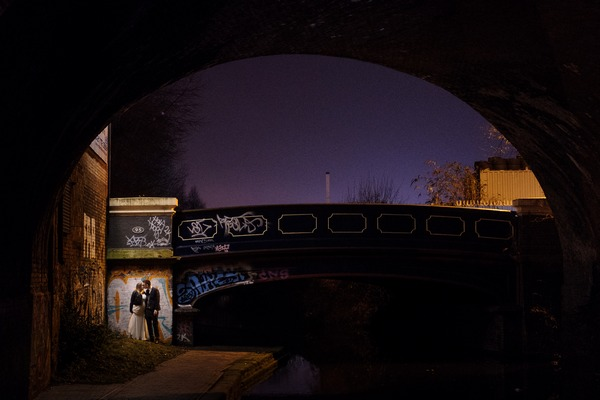 Bride and groom standing by bridge next to canal at night - Picture by Simon Dewey Photography