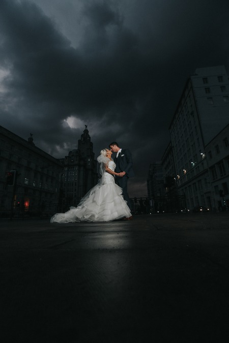 Bride and groom in middle of road with dark clouds overhead - Picture by Squashed Apple