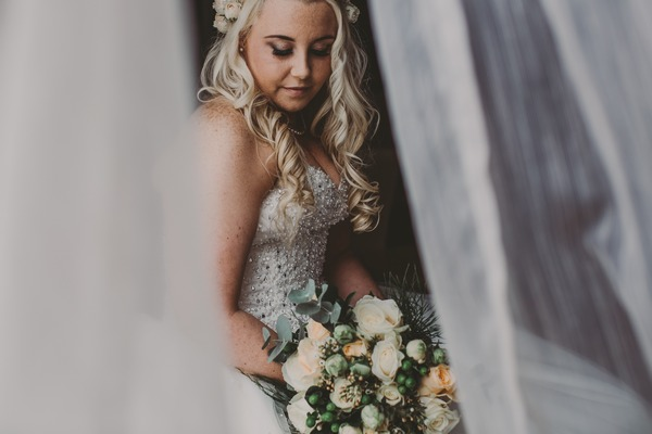 Bride sitting holding bouquet - Picture by Sally Eaves Weddings