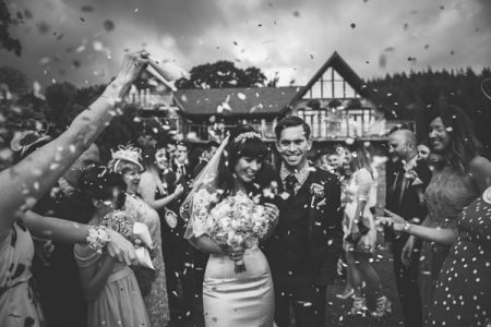 Bride and groom walking through shower of confetti - Picture by Lewis Fackrell Photography