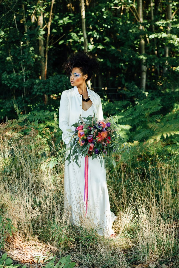 Bride standing in long grass holding bouquet