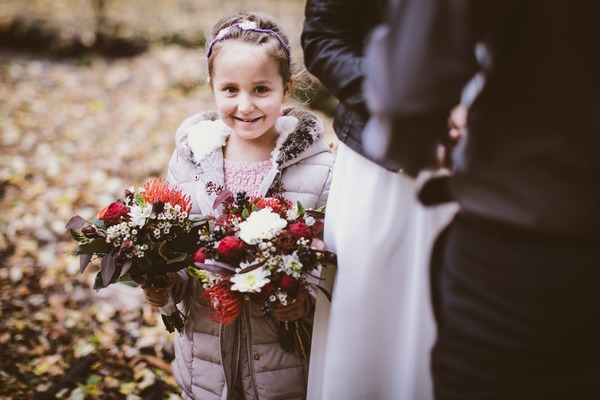 Flower girl smiling holding bouquet
