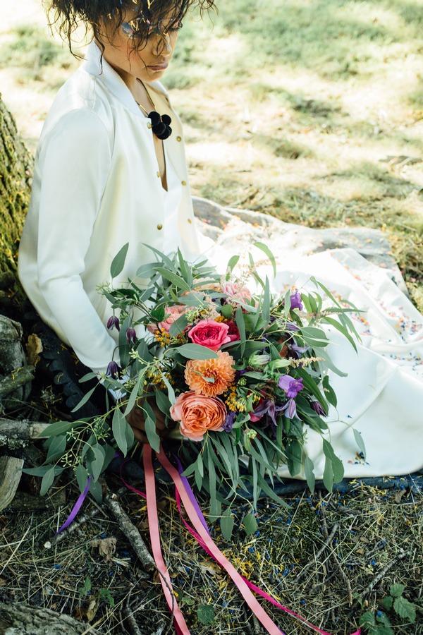 Bride sitting against tree