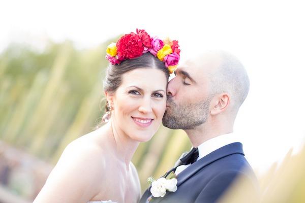 Groom kissing bride with flower crown on cheek
