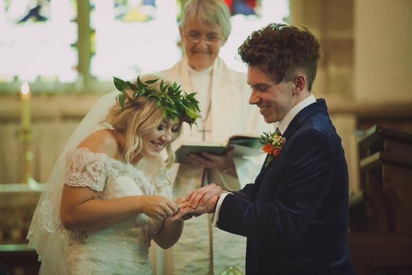 Bride putting ring on groom's finger