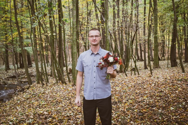 Beat man holding bouquet in forest