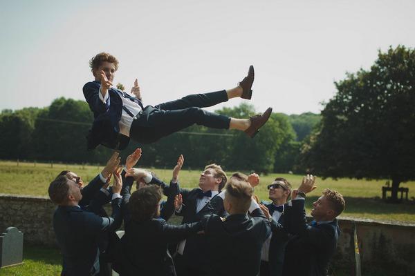 Groomsmen throwing groom in the air