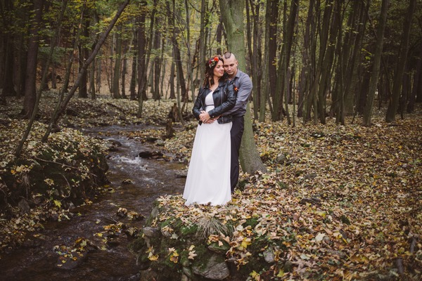 Groom with arms around bride from behind next to stream