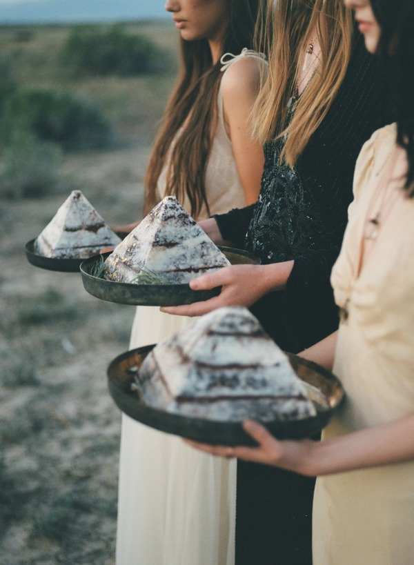 Three brides in row holding pyramid cakes