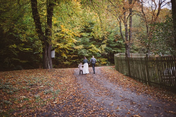 Bride, grrom and flower girl walking through forest clearing