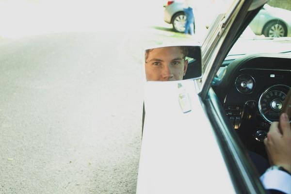 Groom's reflection in wedding car wing mirror