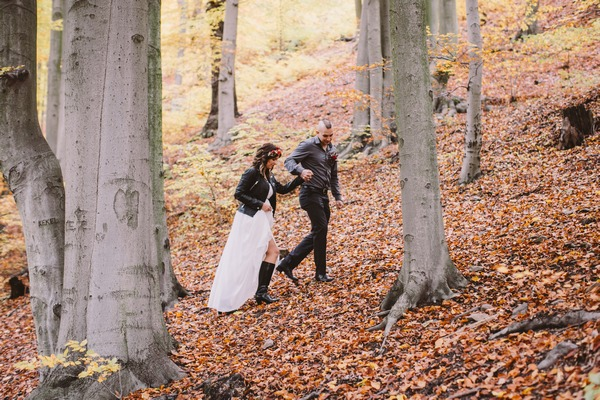 Bride and groom walking up slope in woods