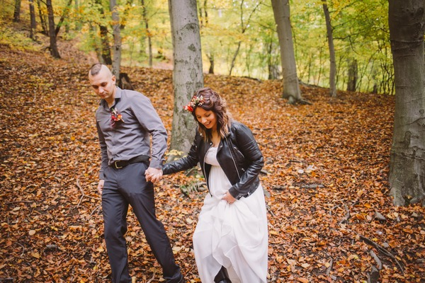 Bride and groom holding hands in forest