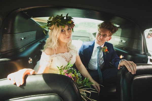Bride and groom in back of wedding car