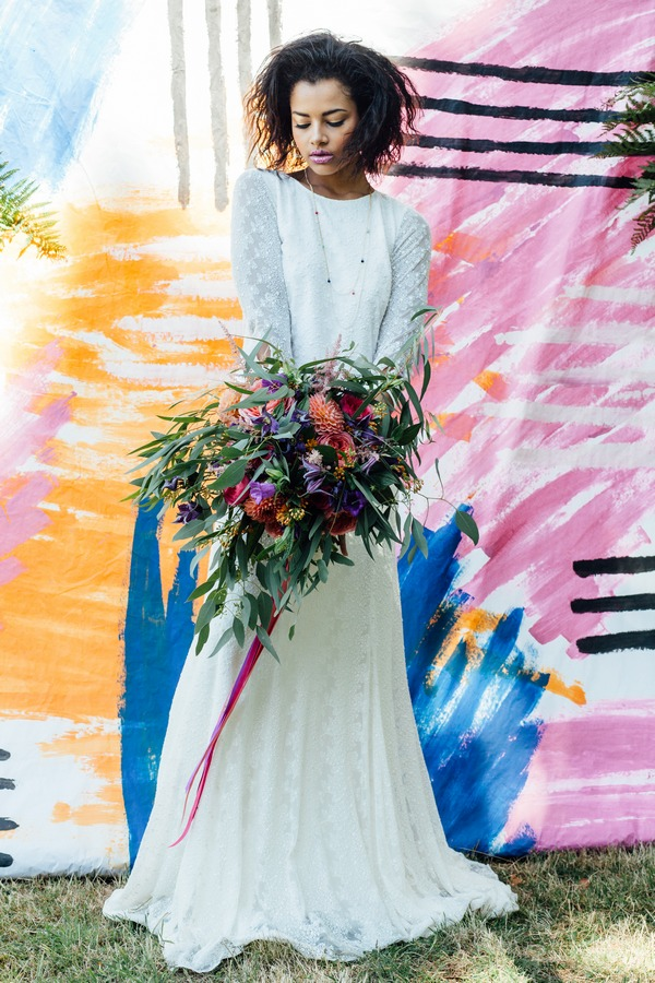 Bride holding bouquet against a colourful backdrop